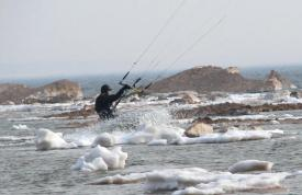 Andy Bolt kiteboarding in ice water in his drysuit